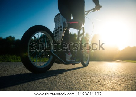 Pretty young brunette woman riding on a push sport on a bike path during lovely summer sunset (color toned image) #1193611102