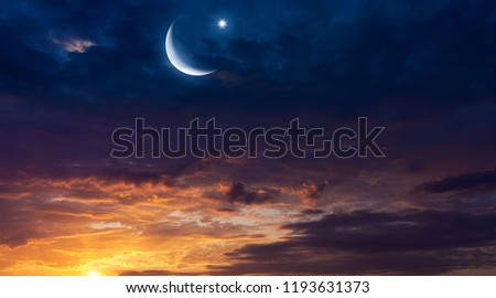 Crescent moon with beautiful sunset background .  Light from sky . Religion background . beautiful sky . Yellow and pink clouds . Sunset and new moon . Prayer time . Generous Ramadan #1193631373