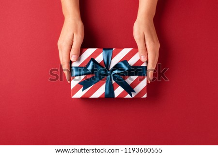 Female's hands holding striped gift box with blue ribbon on red background. Christmas, New Year, Valentine's day and birthday concept. #1193680555
