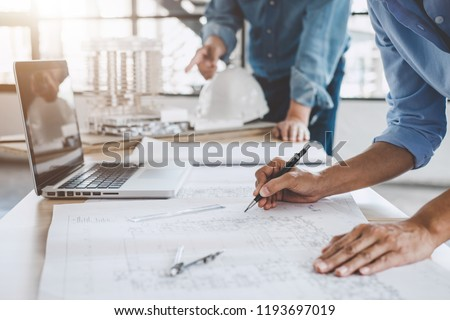 Construction concept of Engineer or architect meeting for project working with partner and engineering tools on model building and blueprint in working site. #1193697019