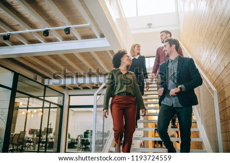 Group of diverse coworkers walking down the stairs in an office #1193724559