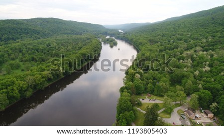 A view of the river surrounded by luscious green trees  #1193805403