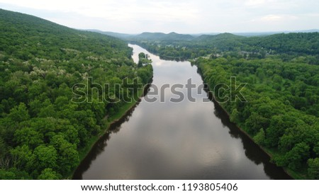 A view of the river surrounded by luscious green trees  #1193805406