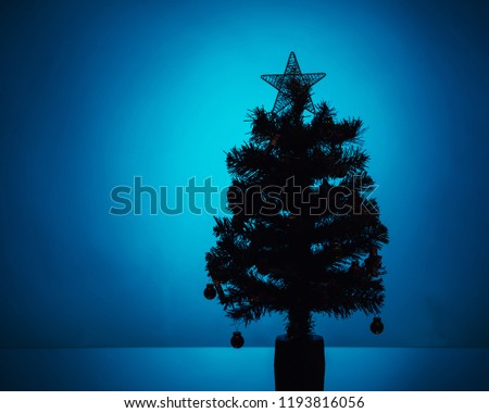 Christmas tree silhouette on blue background