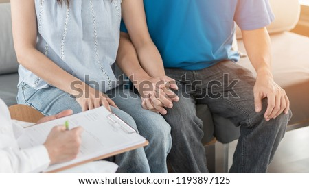 Patient couple consulting with doctor or psychologist on family men and women's medical healthcare therapy, In vitro fertility IVF treatment for infertility, or STD sexual health concept #1193897125