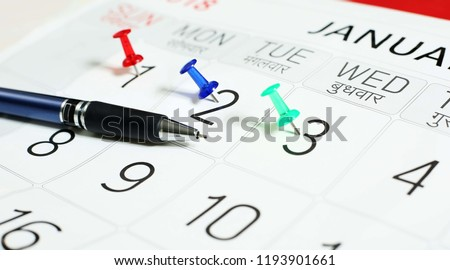 Picture of pen on the calendar with attached all pin.