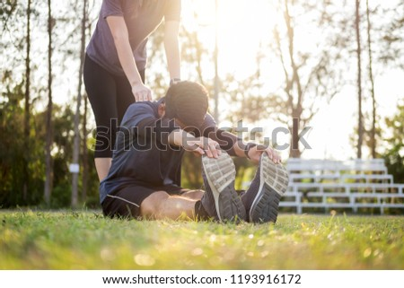 Early morning workout, Fitness couple stretching outdoors in park. Young man and woman exercising together in morning, Relationship healthy lifestyle fitness, sport concept #1193916172