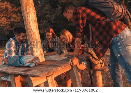 Group of four hikers sitting and resting after hiking in countryside. #1193961802