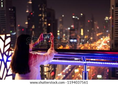Girl taking a photo of Dubai cityscape at night