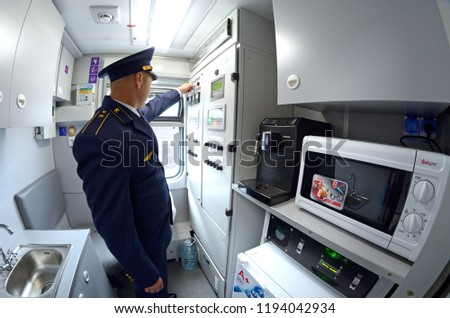 Editorial use only. At the service compartment of a wagon. Conductor turning a tumbler on a control panel, electrical stove, washbasin and refrigerator on a foreground. October 1, 2018. Kiev, Ukraine #1194042934