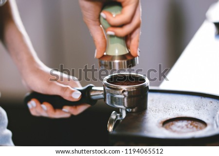 A young pretty slim girl,wearing casual outfit,is cooking coffee in a modern coffee shop. It focuses on the process. #1194065512