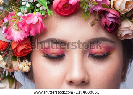 Close up perfect skin face and beautiful eyeshadow, Brunette woman with luxury makeup, Eyelashes. Cosmetic eyeshadow. Close up woman close eye with flower on her head. #1194088051