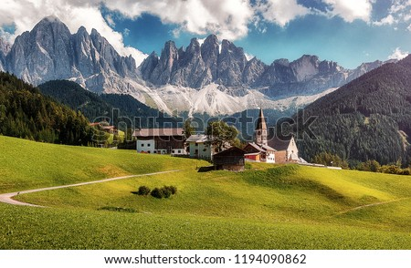 Awesome alpine highlands in sunny day. Breathtaking view of Church of Santa Maddalena with the Odle mountains in the background, is one of the most popular photo spot of Dolomite. Famous World place