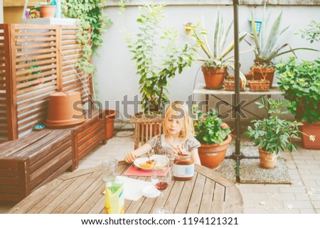female child outdoor sitting table having breakfast - morning routine, eating, hunger concept #1194121321