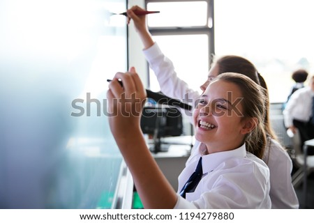 Female High School Students Wearing Uniform Using Interactive Whiteboard During Lesson Royalty-Free Stock Photo #1194279880