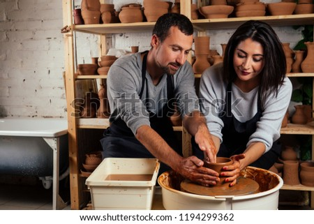 handsome man and happy woman couple in love working on potter wheel while at pottery workshop. husband and wife in the kraft creative studio,young family business shop sculpts pot from clay #1194299362