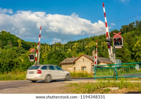 A white passenger car crossing a railroad crossing with barriers. Semaphores in front of the railway crossing. Warning signaling on railway in the Czech Republic. Car arriving at the railway crossing #1194348331