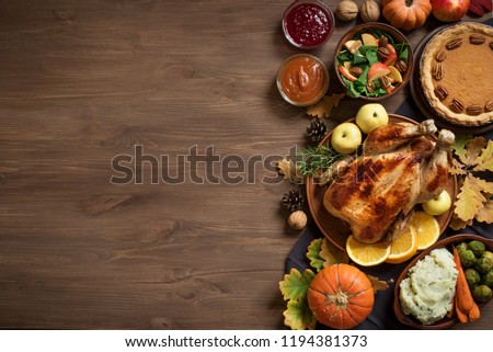 Thanksgiving dinner background with turkey and all sides dishes, pumpkin pie, fall leaves and seasonal autumnal decor on wooden background, top view, copy space. #1194381373