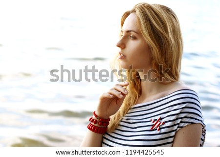 Long-haired blonde girl on the beach by the sea in harmony with nature. The girl is dressed in a nautical style. Sunny day and wind play hair. Vacation and travel. #1194425545