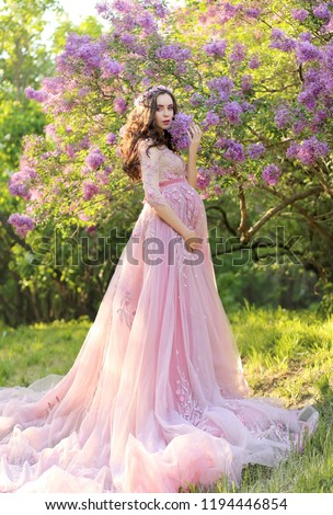 Beautiful young pregnant woman in a luxurious pink dress walking in a park of blossoming lilacs
