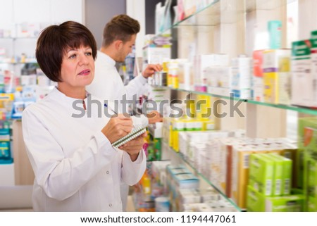 Portrait of two smiling adult pharmacists working in modern farmacy #1194447061