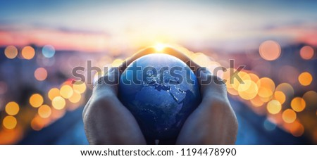 The globe Earth in the hands of man against the night city. Concept on business, politics, ecology and media. Earth day abstract background. Elements of this image furnished by NASA #1194478990