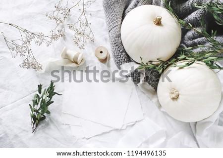 Autumn styled photo. Feminine wedding desktop stationery mockup scene with blank greeting card, eucalyptus, ribbons, white pumpkins and gypsophila flowers. Table background. Thanksgiving. Flat lay.