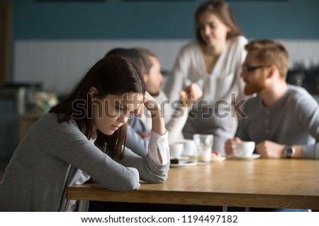 Upset young girl sit alone at coffee table in café feeling lonely or offended, sad female loner avoid talking to people, student outsider suffer from discrimination, lacking friends or company #1194497182