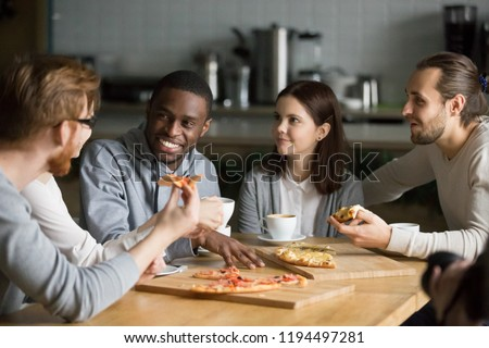 Diverse friends have fun meeting in pizzeria for lunch, multiethnic colleagues eat pizza talking and discussing news in Italian restaurant, young people speak resting in café, hanging out together #1194497281