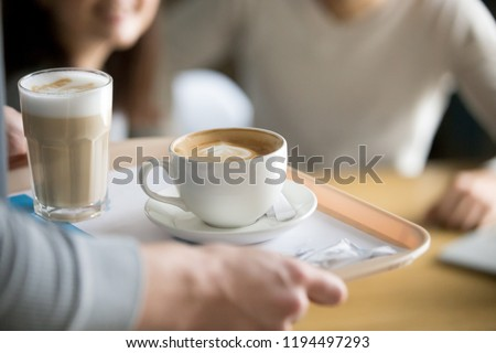 Close up of waiter holding aromatic cappuccino and latte on tray bringing order to café guests, coffeeshop worker give hot drinks to visitors, cups with delicious fresh brewed coffee on platter #1194497293