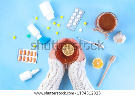 Medications, pills, thermometer, traditional medicine for treating colds, flu, heat on a blue background. Maintenance of immunity. Seasonal diseases. Top view. Medicine flat lay Royalty-Free Stock Photo #1194512323