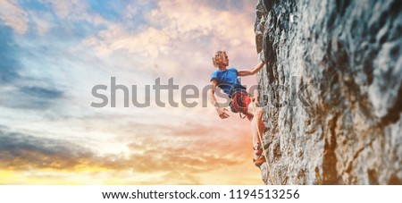 man rock climber with long hair. side view of young man rock climber in bright red shorts resting while climbing the challenging route on the cliff on the colorful down sky background. rock climber #1194513256