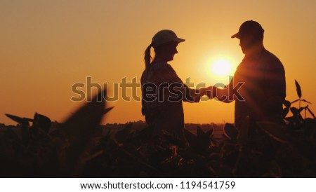 Handshake men and women farmers. On the field at sunset #1194541759