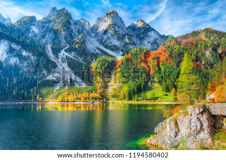 Beautiful view of idyllic colorful autumn scenery with Dachstein mountain summit reflecting in crystal clear Gosausee mountain lake in fall. Salzkammergut region Upper Austria #1194580402