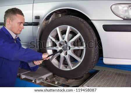Mechanic unscrewing a bolt in a garage #119458087