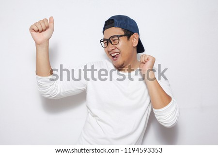 Photo image closeup portrait of a funny young Asian man dancing happily joyful expressing celebrating good news victory winning success gesture over white background