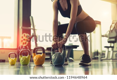 Woman exercise workout at gym fitness training sport with kettlebells weight lifting and legs squat healthy lifestyle bodybuilding. #1194648964