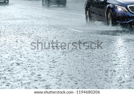 car traffic driving on flooded city road during rain. water splashing from car wheels #1194680206