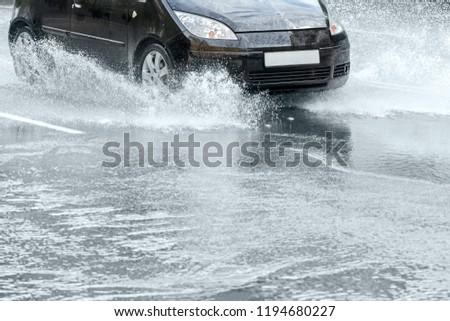 city asphalt road during heavy rain. black car in motion. water splashing from car wheels #1194680227