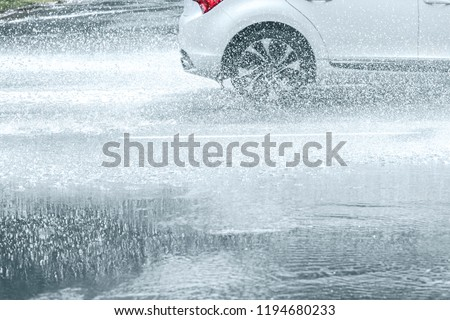 flooded asphalt city road during heavy rain. water spraying from car wheels in motion #1194680233