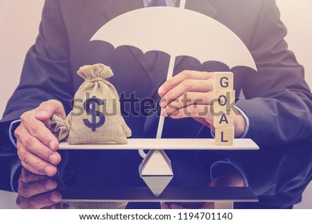 Shareholder's wealth maximization goal and financial protection concept : Dollar bags on a simple basic balance scale with a businessman holds a white umbrella protects or guards properties or assets. #1194701140
