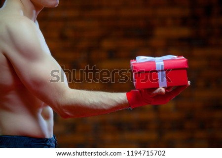 Christmas. Muscular Fighter kickbox boxing Santa Claus With Red Bandages the background of a brick wall. Holds a red gift box #1194715702