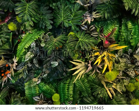 Seamless pattern with artificial tropical leaves and flowers on dark background. Tropic rain forest foliage texture. #1194719665