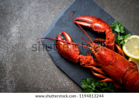 red lobster with vegetable and lemon on black slate plate #1194813244
