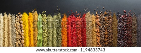 Spices and herbs for website headers. Seasoning scattered on black table, background for packing with food. #1194833743