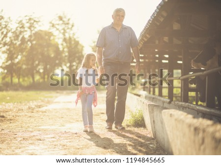 Our time on farm. Granddaughter and grandfather on the farm together.  Copy space.  #1194845665