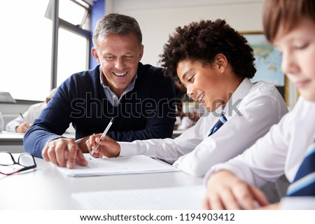 High School Tutor Giving Male Student Wearing Uniform One To One Tuition At Desk #1194903412