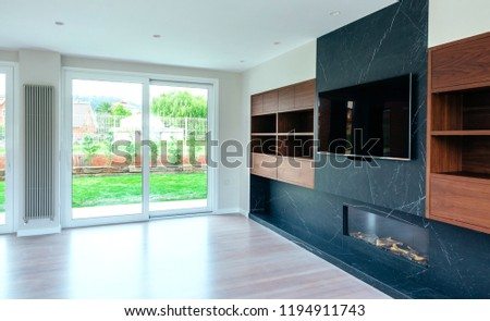 Large living room empty with fireplace and TV #1194911743