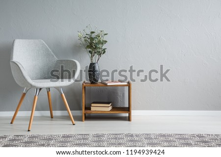 Grey armchair next to wooden table with flowers in flat interior with copy space on the wall. Real photo #1194939424