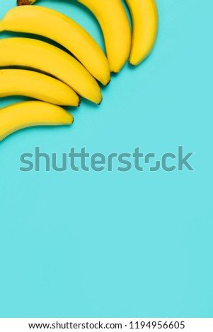 Beautiful yellow bananas on blue colorful background with copy space for text #1194956605